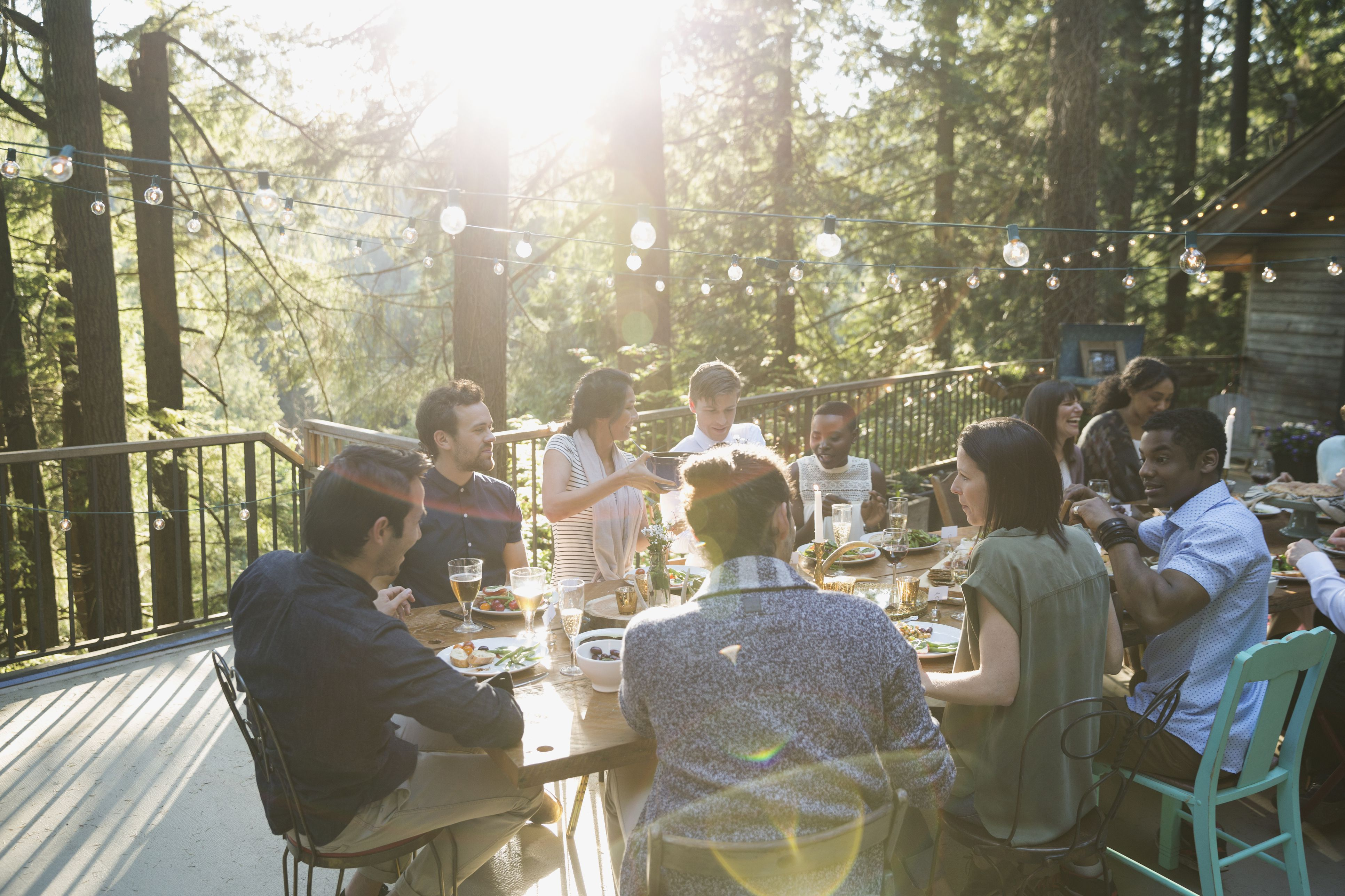 Friends dining around long dining table on balcony at wedding reception