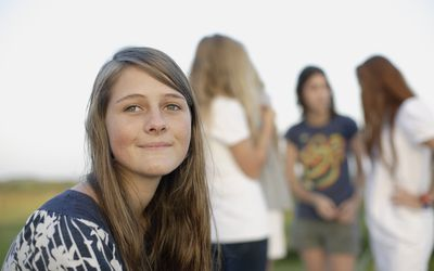 Teen girl sitting apart from another group of girls