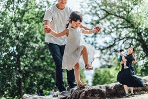 Caring young Asian father holding hands of his little daughter and assisting her to walk along a tree trunk outdoor on a sunny day