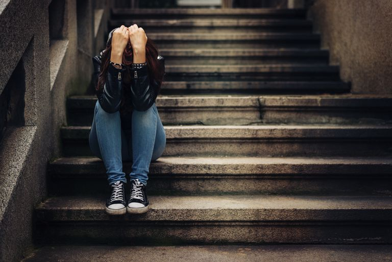 Depressed teen sitting on stairs