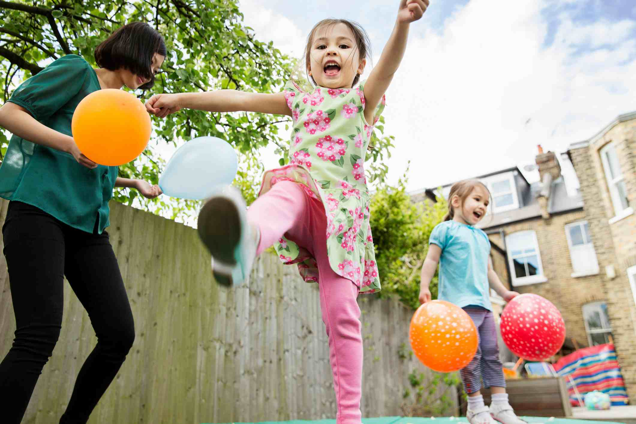 Mother and two daughters playing in garden with balloons