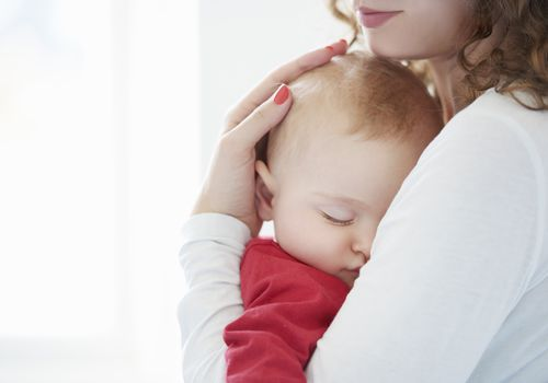 baby sleeping in mother's arms