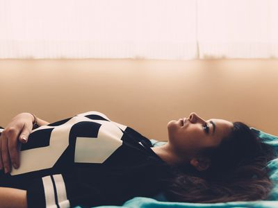 An image of a pregnant woman lying down with a sad expression.