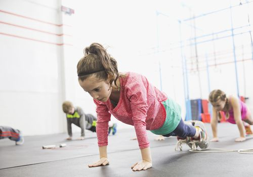 Strength training for kids - girl in gym holding plank position