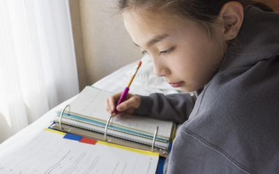 Mixed race girl doing homework on bed