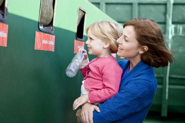 A mother and daughter recycling plastic bottles
