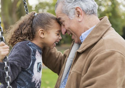 Playful affectionate grandfather and granddaughter on swing at playground