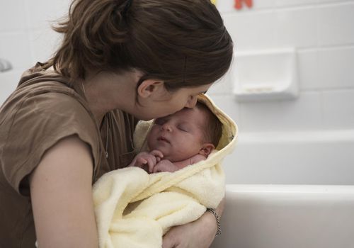 Mother holding baby girl (0-3 months) after bath.