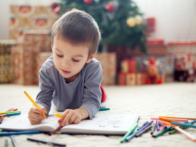 A young boy draws in a book.