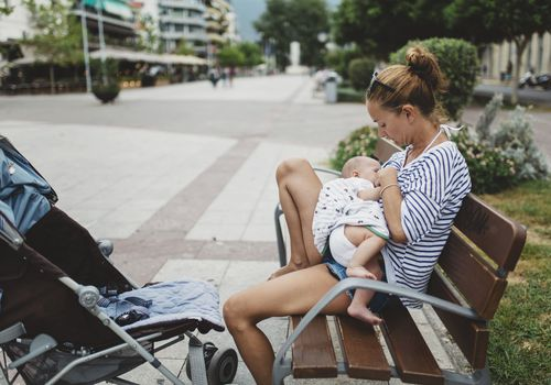 Mother breastfeeding her baby while sitting on an outdoor bench