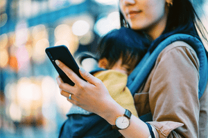 Mother using smartphone while shopping with daughter