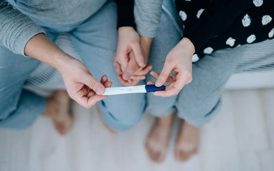 Couple holding hands and looking at a pregnancy test.