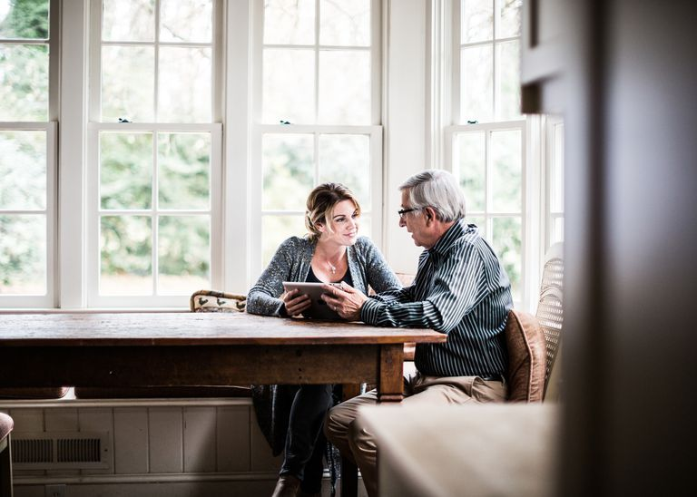 Adult woman and senior man talking at a kitchen table