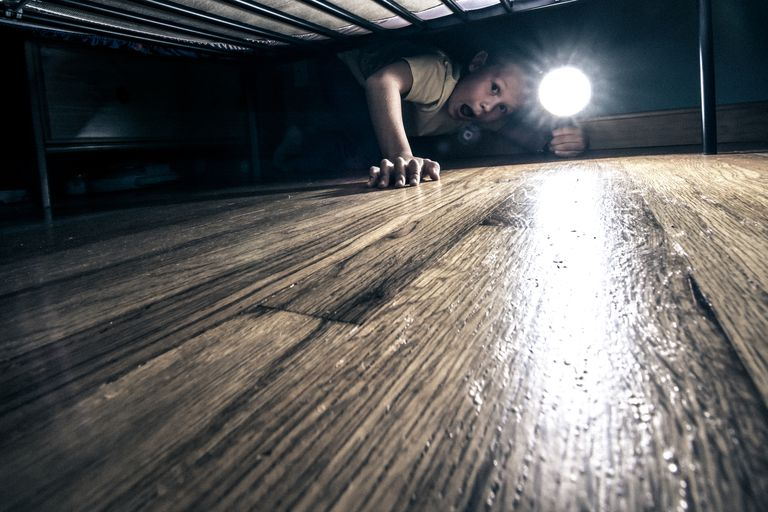 Boy checking under his bed with a flashlight