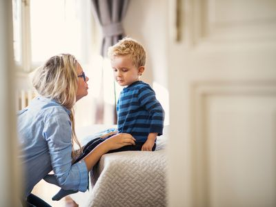 A mother talking to her toddler son inside in a bedroom