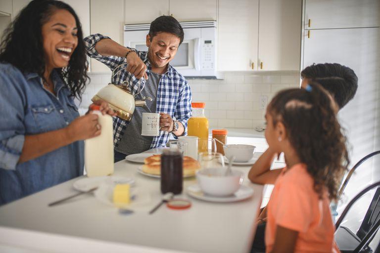 Happy family of four having breakfast in kitchen
