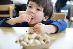 A young boy sits at a table and eats a peanut from a bowl with many peanuts.