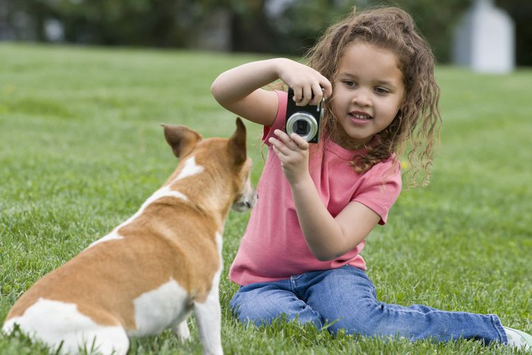 A girl using a camera outside.