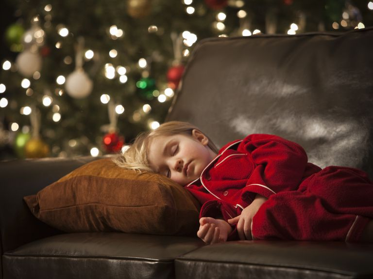 child sleeping on sofa at Christmas - holiday stress in children