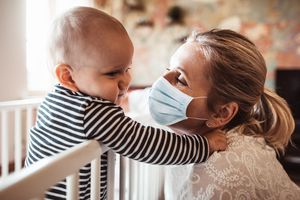 new mother playing with son wearing a mask