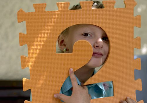 Little girl holding the foamed plastic frame of a number in front of her face