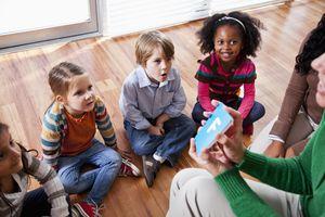 Preschool children with teachers looking at flashcards