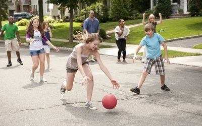 Kids playing kickball in street