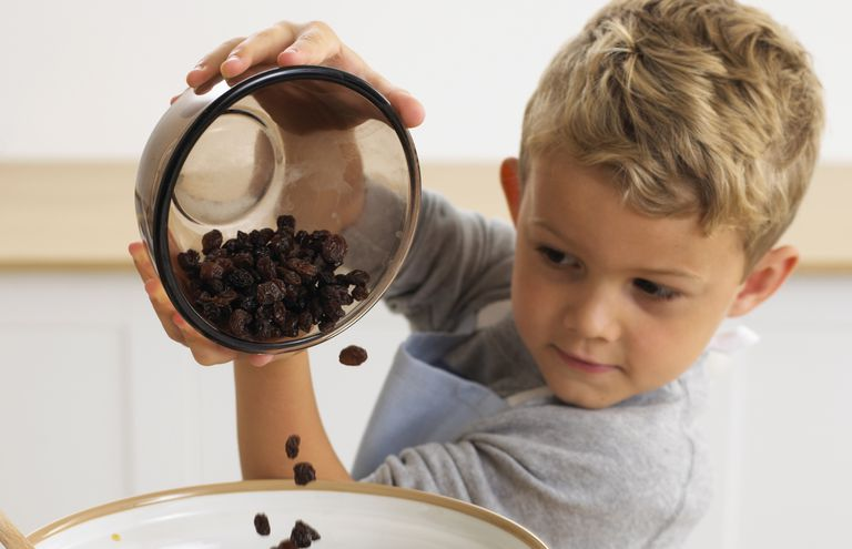 Boy pouring raisins into bowl of muesli mixture, 4 years