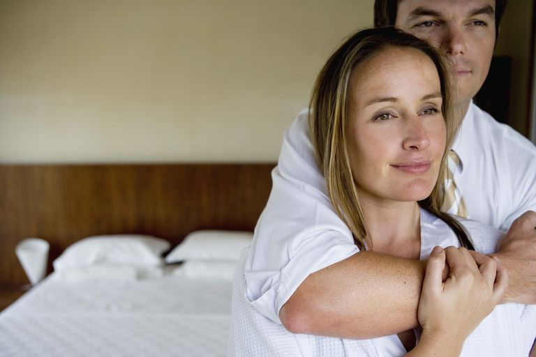 Couple standing in fornt of bed embracing