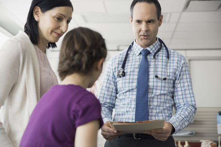 Pediatrician talking with patient and mother in office