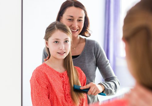 Mother brushing daughter's hair