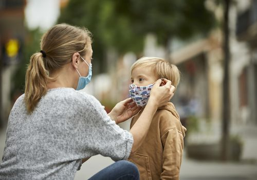 mom putting a mask on her young son