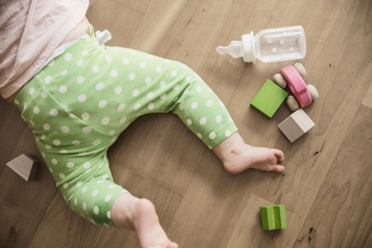 Baby and bottle on floor with blocks