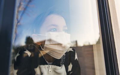Little girl with covid-19 looks out a window