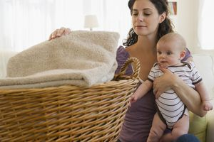 Woman folding laundry while holding a baby
