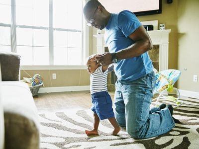 Man helping his baby learn to walk