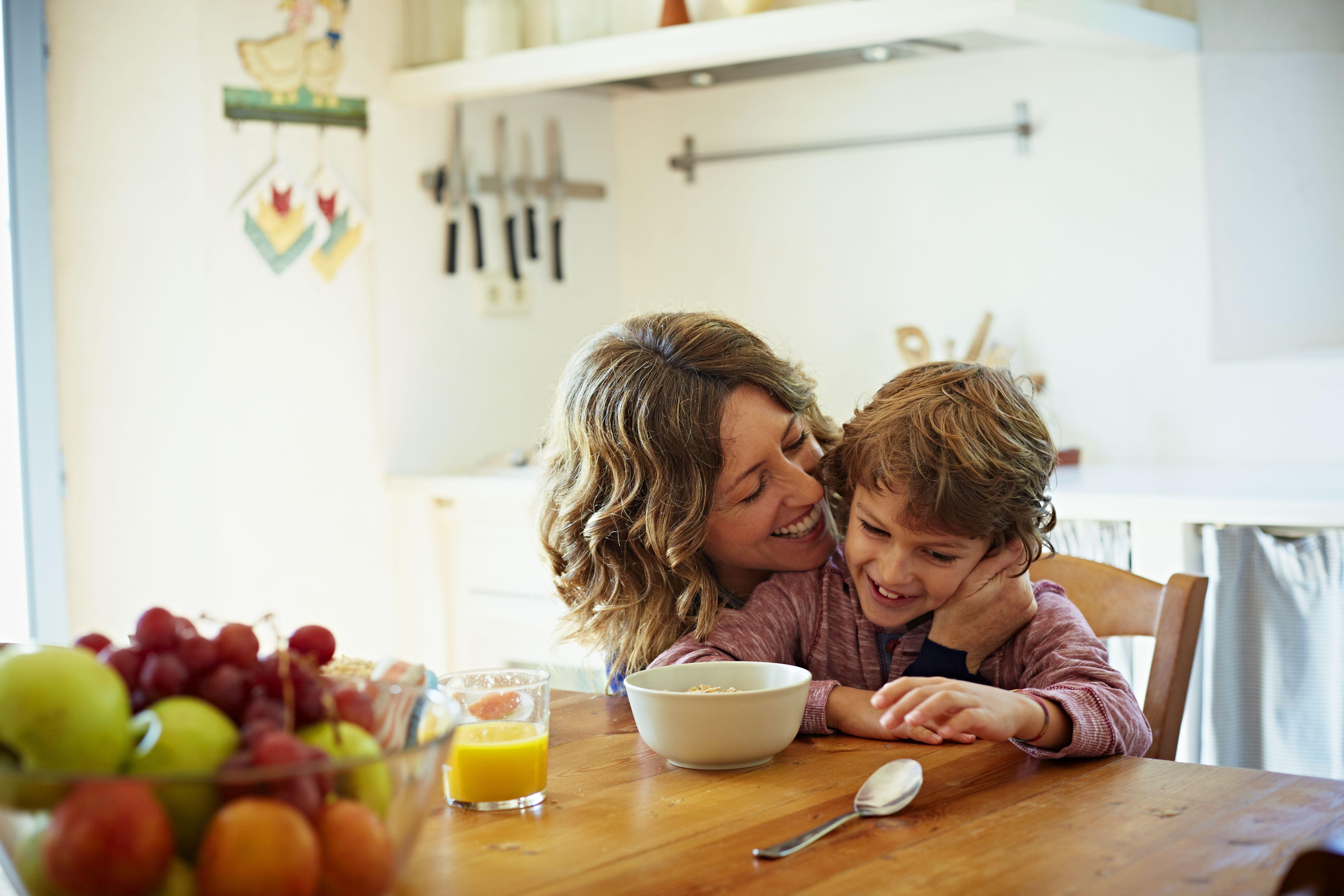 Happy mother embracing son having breakfast