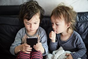 two young children looking at a smart phone
