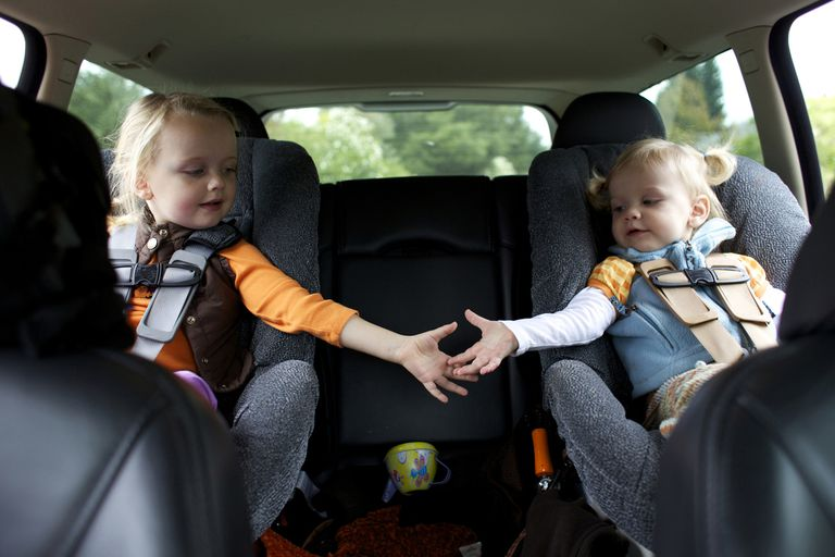 sisters holding hands in back seat of car