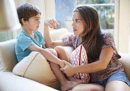 mother sternly talking to young son on couch