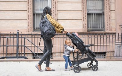 Woman on city street pushing a stroller with a backpack on her back. There is a toddler walking along with the stroller.