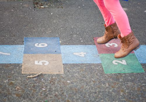Girl playing Hop scotch in playground.