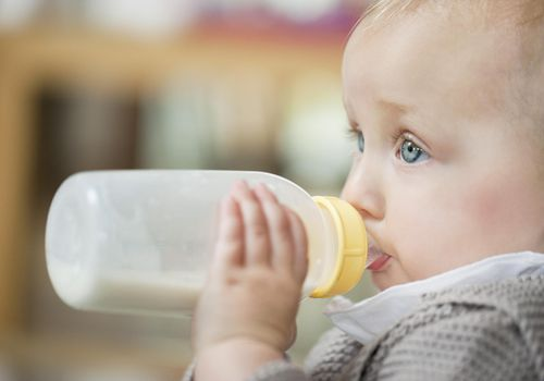 Close-up of a baby girl feeding milk